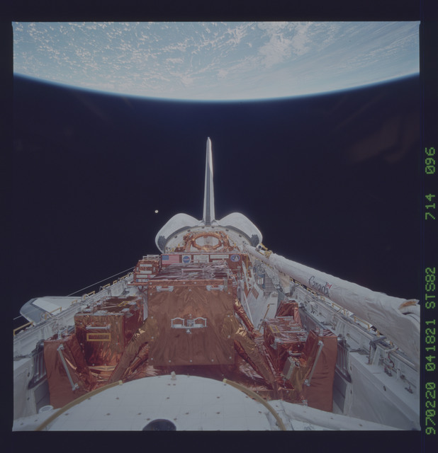 STS082-714-096 - STS-082 - Payload bay view with orbiter tail pointing at the Earth limb