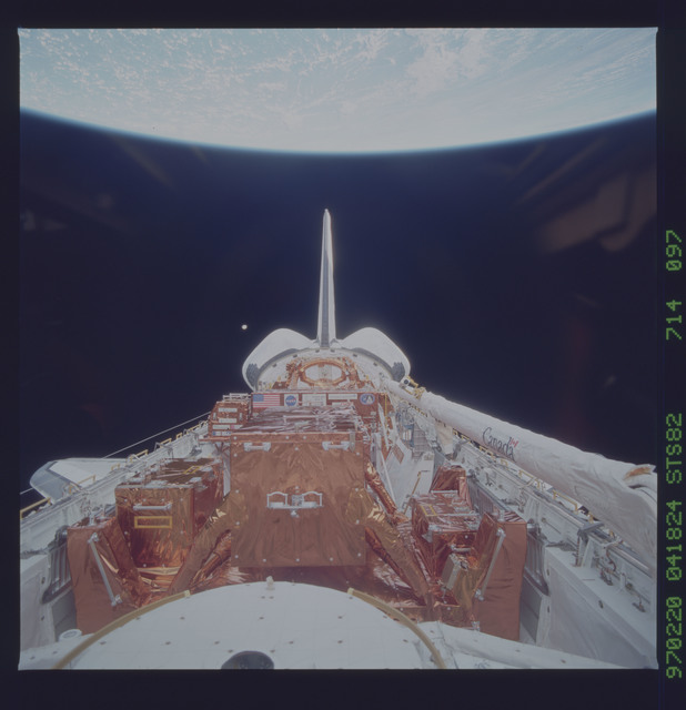STS082-714-097 - STS-082 - Payload bay view with orbiter tail pointing at the Earth limb