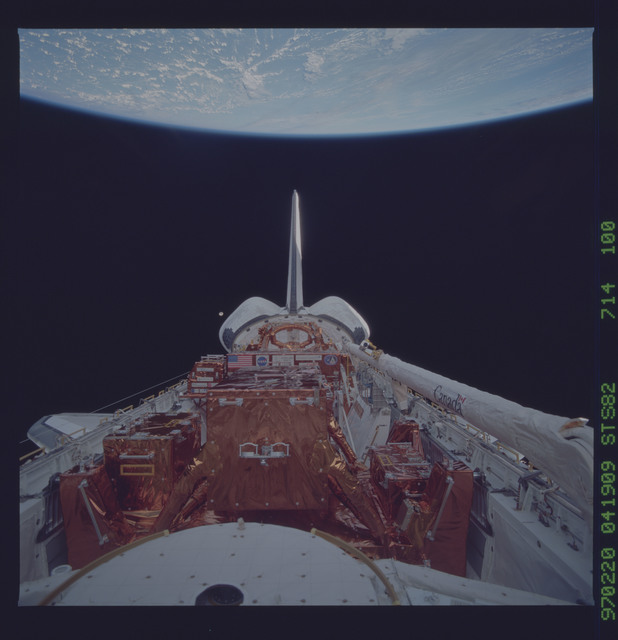 STS082-714-100 - STS-082 - Payload bay view with orbiter tail pointing at the Earth limb