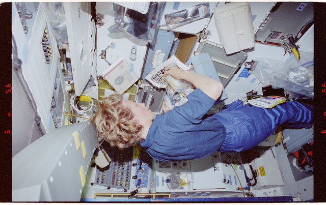 STS083-451-029 - STS-083 - Pilot Still unpacks food packets on middeck