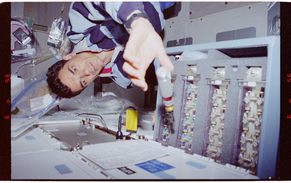 STS083-489-028 - STS-083 - HHDTC - PS Linteris unpacks hardware from its middeck locker