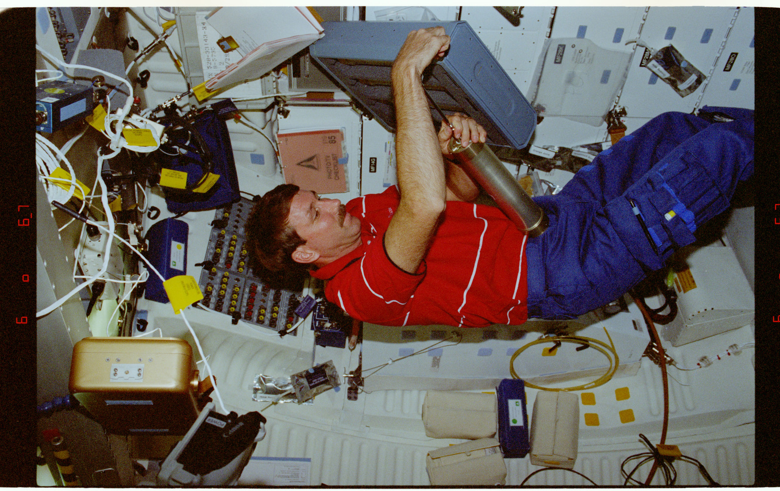 STS085-315-022 - STS-085 - PCG-STS - Rominger sets up middeck experiment