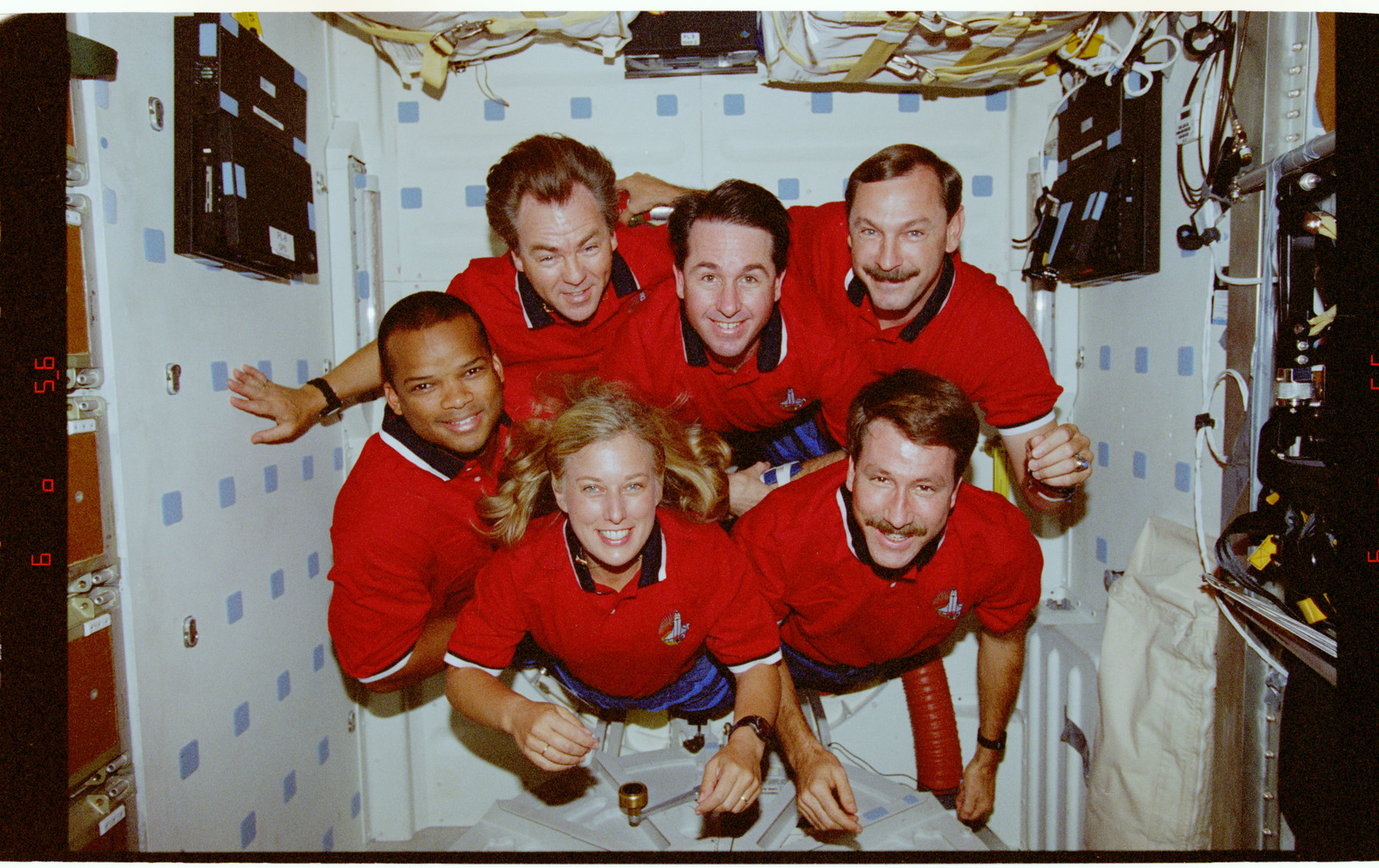 STS085-320-009 - STS-085 - STS-85 crew portraits in the middeck hatch and in front of lockers