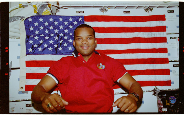 STS085-353-005 - STS-085 - Curbeam poses for photograph in front of American flag