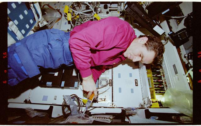 STS087-334-028 - STS-087 - CUE, Kadenyuk holds a tube and syringe