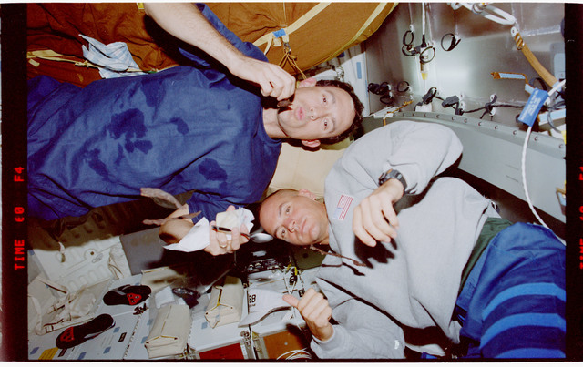 STS088-342-034 - STS-088 - Newman and Sturckow on the middeck with beef jerky