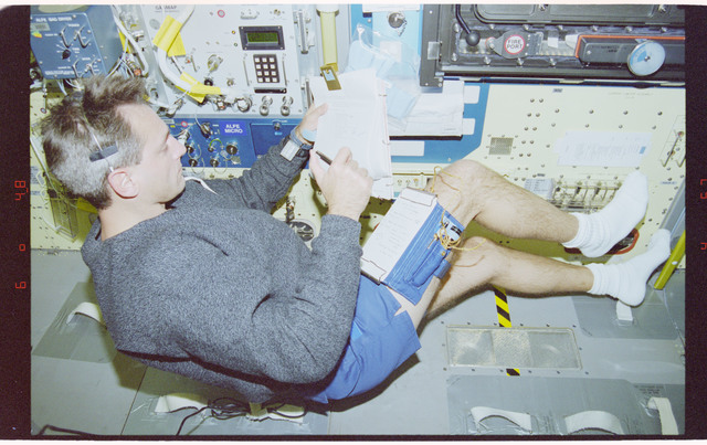 STS090-323-035 - STS-090 - Linnehan in Spacelab reviewing checklist