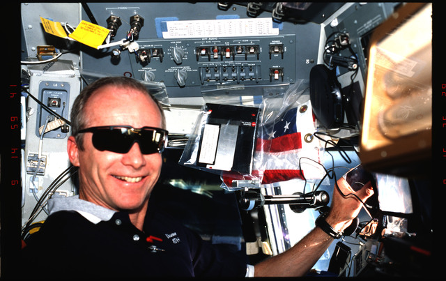 STS091-349-004 - STS-091 - Precourt smiles in the flight deck wearing sunglasses