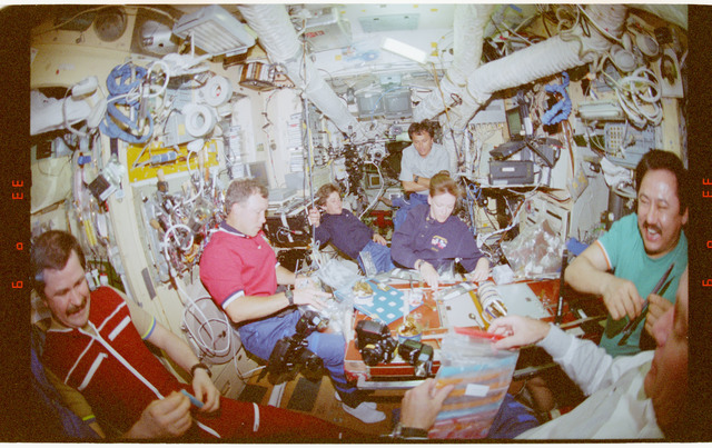 STS091-367-014 - STS-091 - STS-91 and Mir 25 crewmembers share a meal in the Mir Space Station