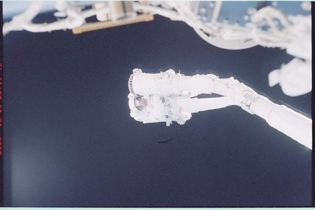 STS092-396-001 - STS-092 - Lopez-Alegria holds onto the shuttle RMS during EVA