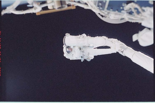STS092-396-002 - STS-092 - Lopez-Alegria holds onto the shuttle RMS during EVA