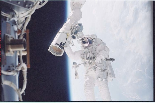 STS092-396-004 - STS-092 - McArthur holds onto the shuttle RMS during EVA