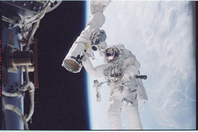 STS092-396-005 - STS-092 - McArthur holds onto the shuttle RMS during EVA
