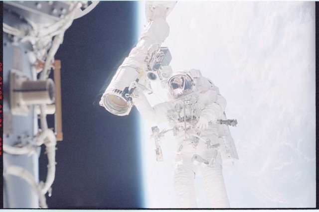 STS092-396-006 - STS-092 - McArthur holds onto the shuttle RMS during EVA