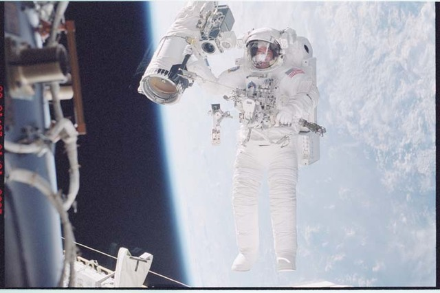 STS092-396-007 - STS-092 - McArthur holds onto the shuttle RMS during EVA