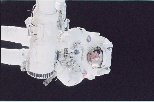 STS092-397-033 - STS-092 - McArthur holds onto the RMS arm during an EVA