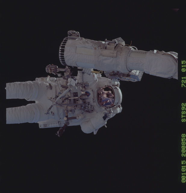 STS092-721-015 - STS-092 - MS Chiao holds the RMS arm during an EVA