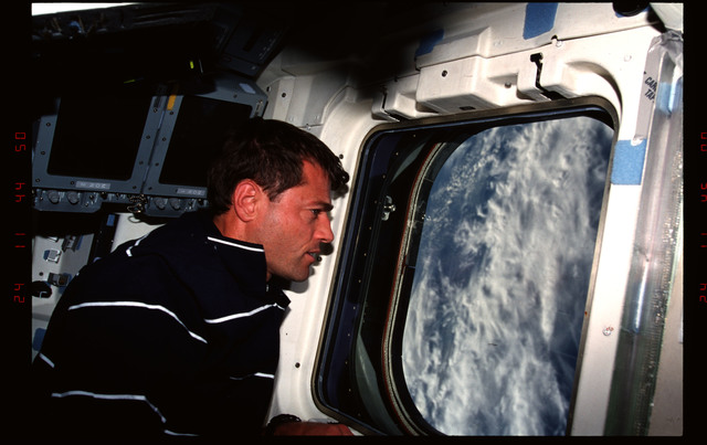 STS093-301-018 - STS-093 - Pilot Ashby looks at the Earth through the windows on the aft flight deck