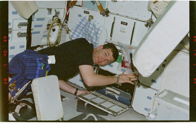 STS096-354-010 - STS-096 - PLT Husband unpacks locker while on the middeck
