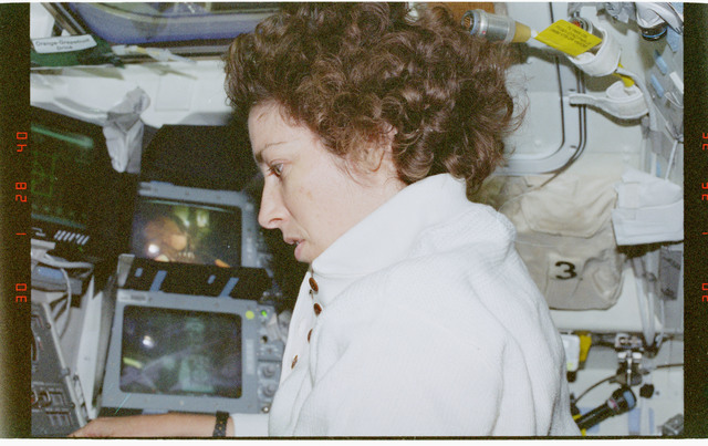 STS096-356-001 - STS-096 - MS Ochoa prepares to operate the RMS arm during EVA