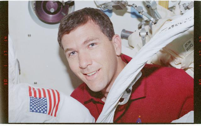 STS096-360-033 - STS-096 - PLT Husband adjusts EMU for crewmate prior to EVA