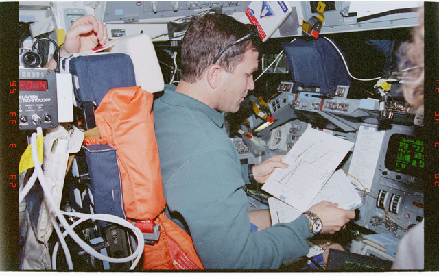 STS096-361-018 - STS-096 - PLT Husband with checklist at commanders station on forward flight deck