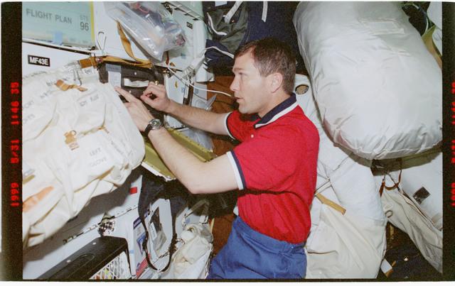 STS096-376-019 - STS-096 - PLT Husband unpacks locker on Discovery's middeck