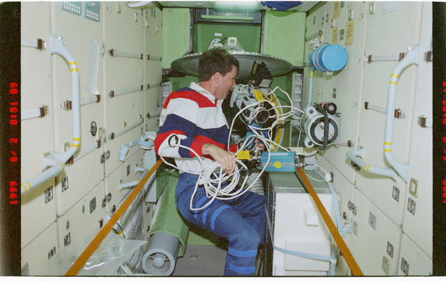 STS096-379-025 - STS-096 - PLT Husband in FGB/Zarya module with camcorder and cables