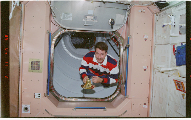 STS096-382-014 - STS-096 - CDR Rominger in hatch with ISS ship's bell