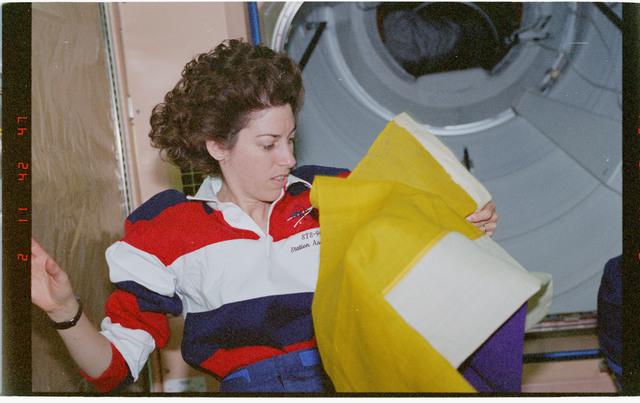 STS096-382-019 - STS-096 - MS Ochoa unfurls National Women's Party banner in Node 1/Unity module