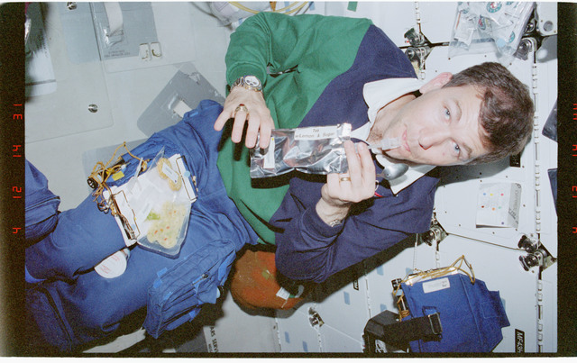 STS096-386-025 - STS-096 - PLT Husband with drink packets on the middeck