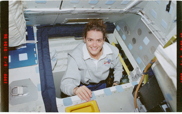 STS096-392-016 - STS-096 - MS Payette looks up from intradeck hatch into flight deck
