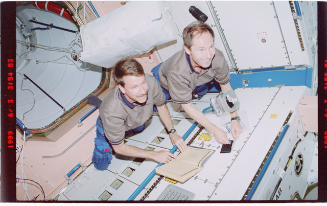 STS096-407-025 - STS-096 - CDR Rominger and MS Tokarev sign ships log in Node 1/Unity module