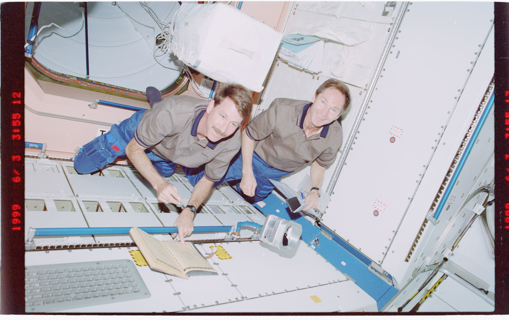STS096-407-028 - STS-096 - CDR Rominger and MS Tokarev sign ships log in Node 1/Unity module
