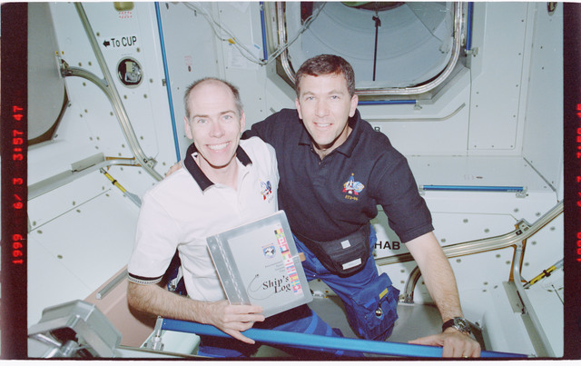 STS096-407-033 - STS-096 - STS-96 crew poses with ships log in Node 1/Unity module