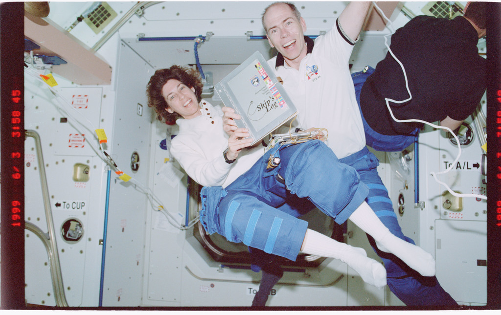 STS096-407-034 - STS-096 - STS-96 crew poses with ships log in Node 1/Unity module