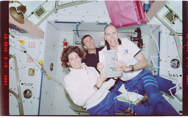 STS096-407-036 - STS-096 - STS-96 crew poses with ships log in Node 1/Unity module