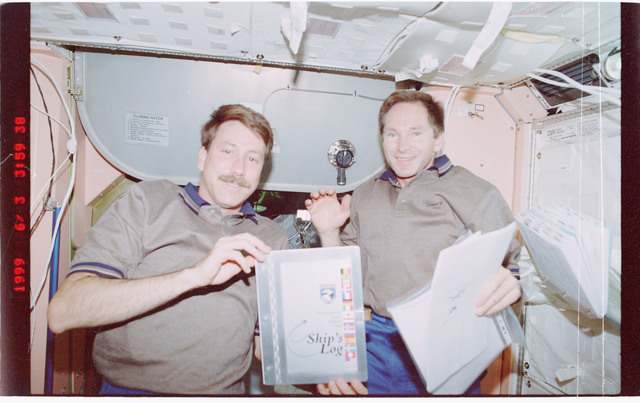 STS096-407-037 - STS-096 - STS-96 crew poses with ships log in Node 1/Unity module