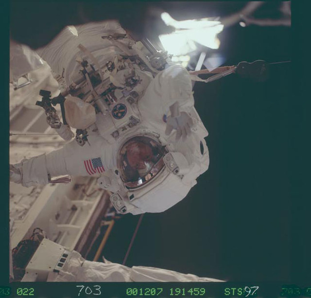STS097-703-022 - STS-097 - View of MS Noriega waves to the camera during the third EVA of STS-97