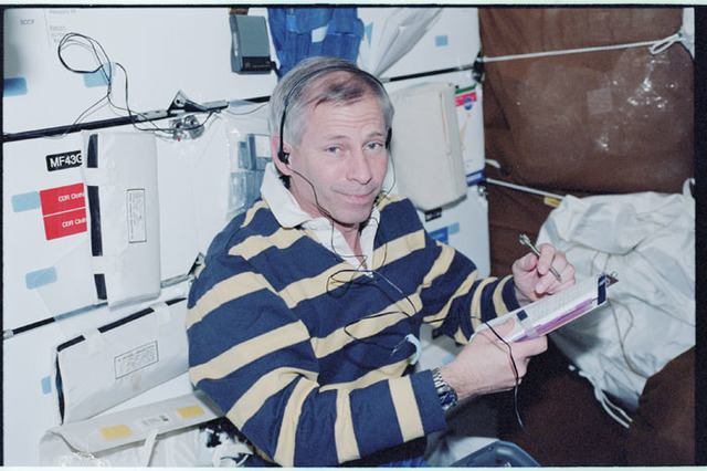 STS098-345-005 - STS-098 - CDR Cockrell listens to music on Atlantis' middeck