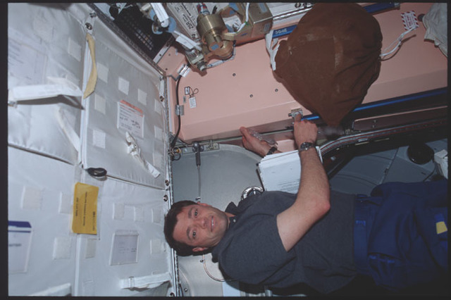 STS100-389-015 - STS-100 - Pilot Ashby finishes installing a dosimeter in Node 1 during STS-100