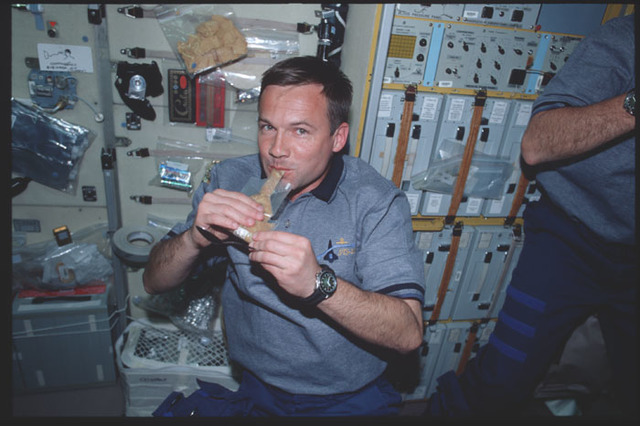 STS100-390-005 - STS-100 - MS Lonchakov with a bag of food in the Service Module during STS-100