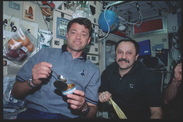 STS100-390-007 - STS-100 - Ashby and Usachev share a meal in the Service Module during STS-100