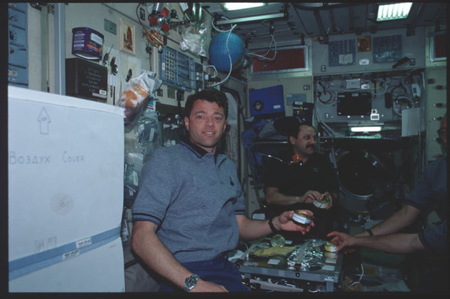 STS100-390-012 - STS-100 - Expedition Two and STS-100 crews share a meal in the Service Module during STS-100