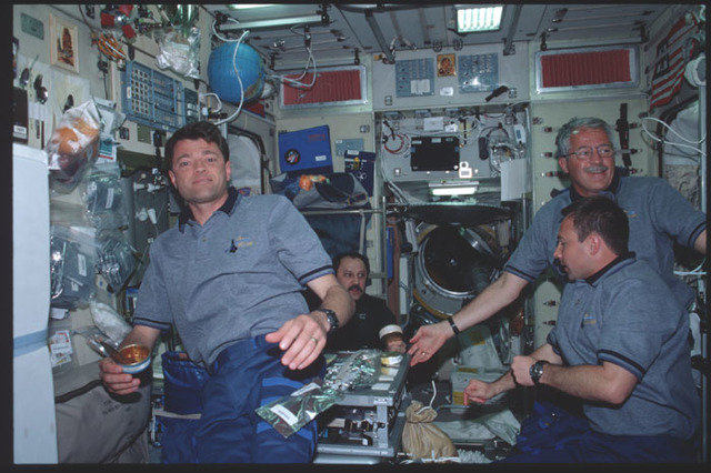 STS100-390-014 - STS-100 - Expedition Two and STS-100 crews share a meal in the Service Module during STS-100
