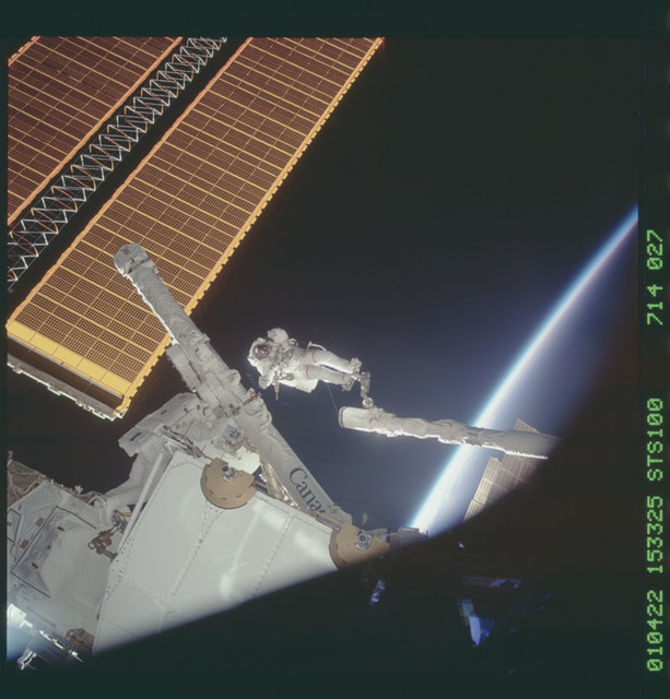 STS100-714-027 - STS-100 - MS Hadfield and MS Parazynski raise the SSRMS from the SLP during an EVA for STS-100