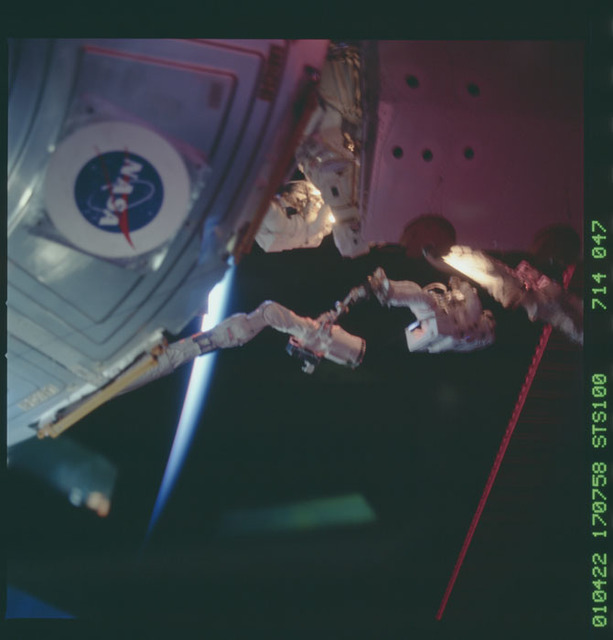 STS100-714-047 - STS-100 - MS Hadfield and MS Parazynski raise the SSRMS from the SLP during an EVA for STS-100