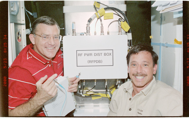 STS101-388-001 - STS-101 - MS Voss and PLT Horowitz with Early Comm power unit in Node 1/Unity module