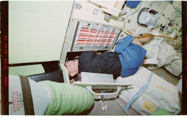 STS101-389-020 - STS-101 - MS Voss works behind panel in FGB/Zarya module