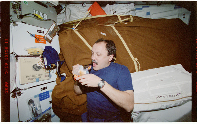 STS101-399-014 - STS-101 - MS Usachev eats shrimp cocktail on middeck